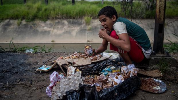 Un niño come de los restos de la basura en Caracas - EFE